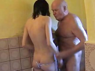 young brunette helps grandpa get a bathroom and