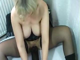 this busty milf is using a big brown sex toy in